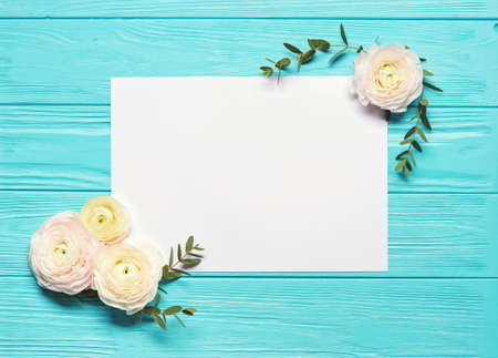 Bright mint background with white gentle ranunculus flowers and blank paper with place for text