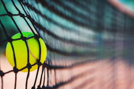 Tennis ball in net on court closeup