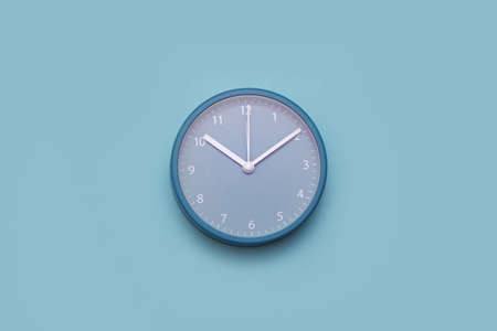 Modern alarm clock on pastel blue background. Minimal concept.
