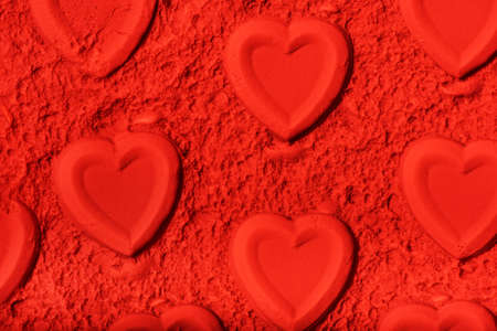 Background made of hearts stamped on red powder. Stock Photo