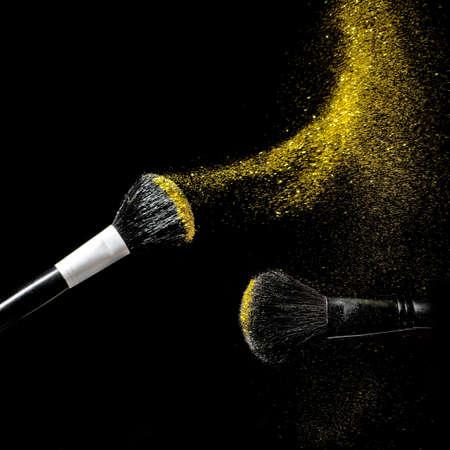 Make-up brush with gold powder explosion on black background. Stock Photo