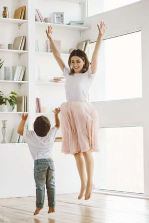 Beautiful mother and cute little son are dancing together at home. 写真素材 - 143266699