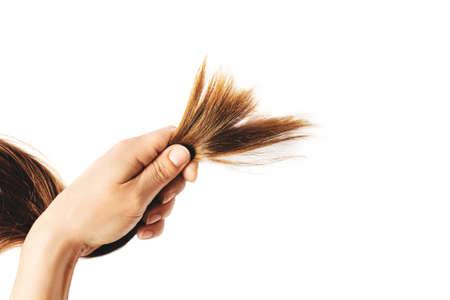 Woman hand holding hair.