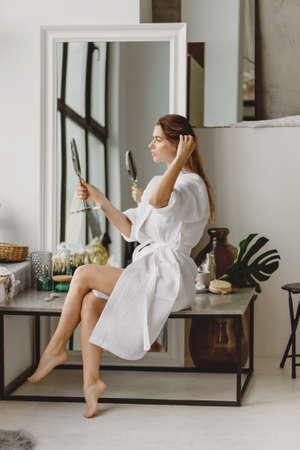 Beautiful long-haired woman enjoying makeup in the morning.