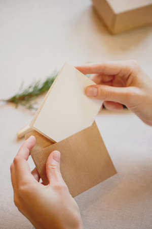 Close up of female hands putting a card into a craft paper envelope.