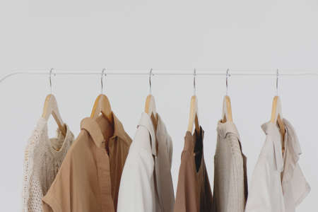 Collection of female clothes hanging on a rack.