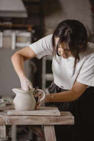 Female potter making a clay jug.