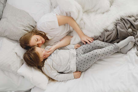 Mother and daughter are lying on bed in pajamas. 版權商用圖片