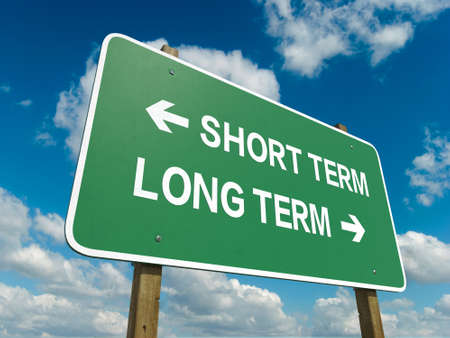 long term: A road sign with short term long term words on sky background Stock Photo