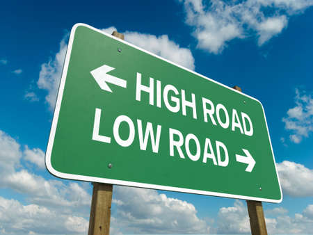 A road sign with high road low road words on sky background photo