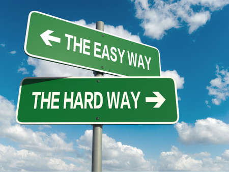 A road sign with easy way hard way words on sky background photo