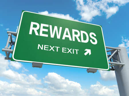 recompense: A road sign with rewards words on sky background Stock Photo