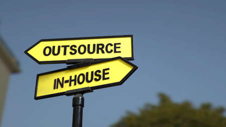 A road sign with outsource and  inhouse words