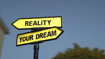 A road sign with reality  and dream words