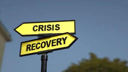 A road sign with crisis  and recovery words