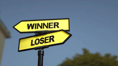 A road sign with winner  and loser words