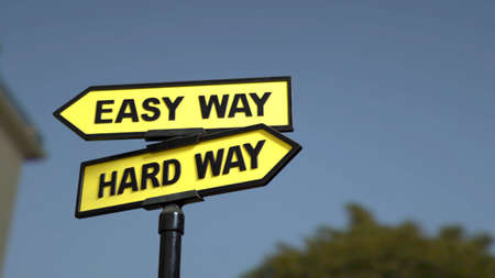 A road sign with easy way  and  hard way words