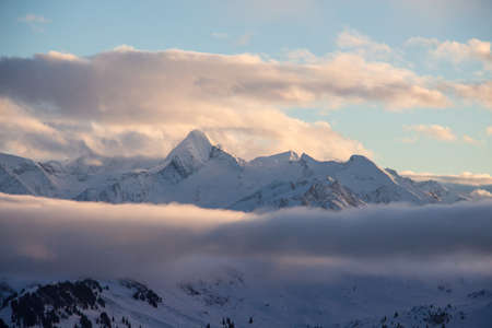 Kitzsteinhorn dark mood weather sky snowy mountainscape landscape winter. blue hour light glimmering foggy. perfect light and sky.
