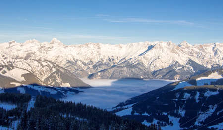 sunset view steinernes meer Saalbach hinterglemm leogang with snowy mountains in sunset light and fog in the valley. misty mood and perfect winter and autumn light.