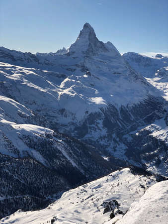 Perfect view of the Matterhorn in Zermatt at a perfect sunny day, with blue sky and perfect light. The snowy Swiss mountains and landscape in winter is extraordinary. After a long skiing day these views are incredible. Stock fotó
