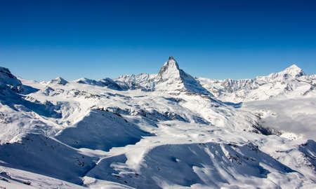 Perfect view of the Matterhorn and glacier in Zermatt at a perfect sunny day, with blue sky and perfect light. The snowy Swiss mountains and landscape in winter is extraordinary. After a long skiing day these views are incredible.