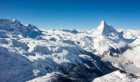 Perfect view of the Matterhorn and glacier and monte rosa in Zermatt sunset view, with blue sky and perfect light. The snowy Swiss mountains and landscape in winter is extraordinary. After a long skiing day these views are incredible.