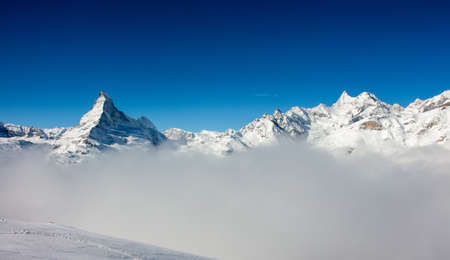 Perfect view of the Matterhorn in Zermatt at a perfect sunny day, with blue sky and perfect light. In the valley sea of clouds fog dust with matterhorn emerging from the clouds. The snowy Swiss mountains and landscape in winter is extraordinary. After a long skiing day these views are incredible. Stock fotó