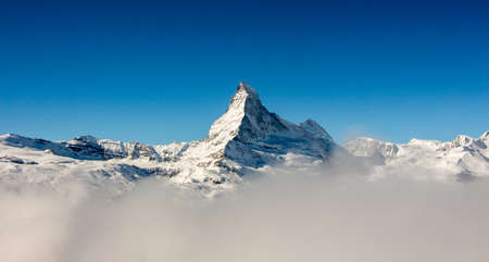 Perfect view of the Matterhorn in Zermatt at a perfect sunny day, with blue sky and perfect light. In the valley sea of clouds fog dust with matterhorn emerging from the clouds. The snowy Swiss mountains and landscape in winter is extraordinary. After a long skiing day these views are incredible. Stock Photo