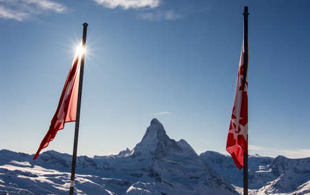 Perfect view of the Matterhorn in Zermatt at sunset with backlight and the sun behind the mountain. The snowy Swiss mountains and landscape in winter is extraordinary. After a long skiing day these views are incredible.