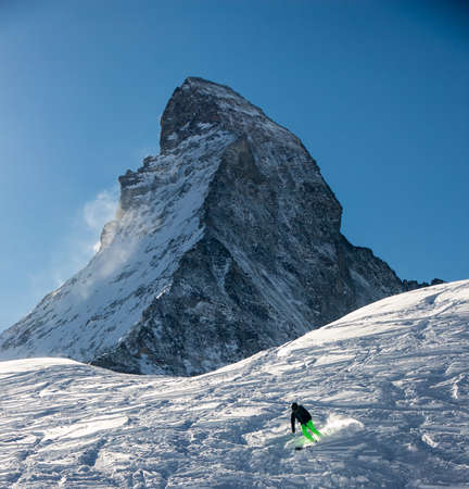 Lonely Skier skiing in front of the Matterhorn in Zermatt at sunset with backlight. The snowy Swiss mountains and landscape in winter is extraordinary. After a long skiing day these views are incredible.