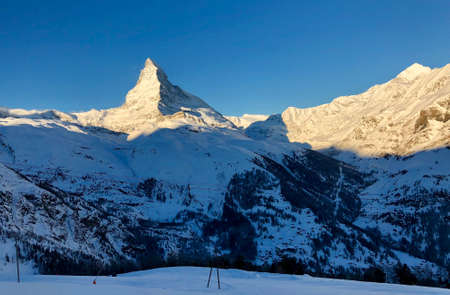 Perfect view of the Matterhorn in Zermatt at sunset, with blue sky and perfect light. The snowy Swiss mountains and landscape in winter is extraordinary. After a long skiing day these views are incredible.