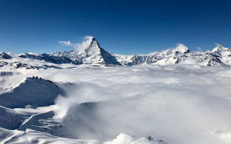 Perfect view of the Matterhorn and gornergrat in Zermatt at a perfect sunny day, with blue sky and perfect light. In the valley sea of clouds fog dust with mountains emerging from the clouds. The snowy Swiss mountains and landscape in winter is extraordinary. After a long skiing day these views are incredible. Stock fotó