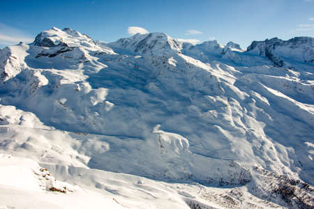 Perfect view of the monte rosa massiv Zermatt at a perfect sunny day, with blue sky and perfect light. The snowy Swiss mountains and landscape in winter is extraordinary. After a long skiing day these views are incredible.