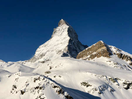 Perfect view of the Matterhorn in Zermatt at a perfect sunny day in sunset red light, with blue sky and perfect light. The snowy Swiss mountains and landscape in winter is extraordinary. After a long skiing day these views are incredible.
