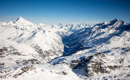 Perfect view of the Mattertal and surrounding mountains like weisshorn in Zermatt sunset view, with blue sky and perfect light. The snowy Swiss mountains and landscape in winter is extraordinary. After a long skiing day these views are incredible.