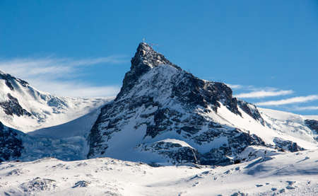 Perfect view of the small Matterhorn in Zermatt at a perfect sunny day, with blue sky and perfect light. The snowy Swiss mountains and landscape in winter is extraordinary. After a long skiing day these views are incredible.