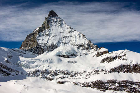 Perfect view of the Matterhorn in Zermatt at a perfect sunny day, with blue sky, clouds and perfect light. The snowy Swiss mountains and landscape in winter is extraordinary. After a long skiing day these views are incredible.