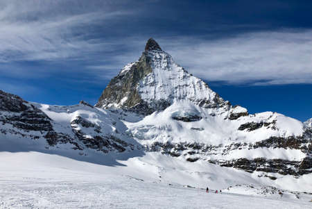 Perfect view of the Matterhorn in Zermatt at a perfect sunny day, with blue sky and perfect light. The snowy Swiss mountains and landscape in winter is extraordinary. After a long skiing day these views are incredible. Zdjęcie Seryjne