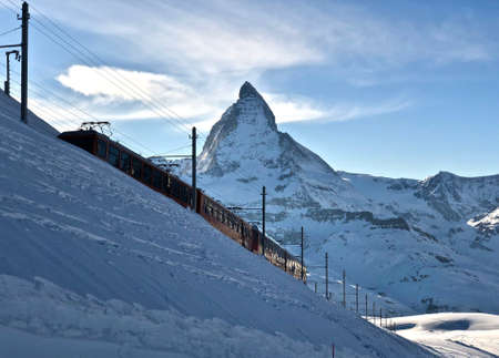 Perfect view of the Matterhorn with railway in front in Zermatt at sunset, with blue sky and perfect light. The snowy Swiss mountains and landscape in winter is extraordinary. After a long skiing day these views are incredible.