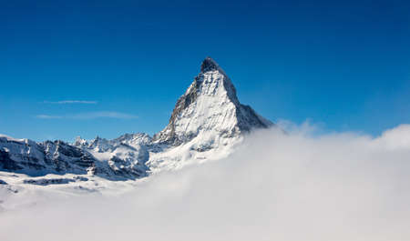 Perfect view of the Matterhorn in Zermatt at a perfect sunny day, with blue sky and perfect light. In the valley sea of clouds fog dust with matterhorn emerging from the clouds. The snowy Swiss mountains and landscape in winter is extraordinary. After a long skiing day these views are incredible. Zdjęcie Seryjne