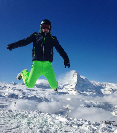 Single person jumping high in front of the matterhorn and blue sky on a sunny day. After skiing perfect feeling describing joy leisure vacation. Zermatt Switzerland jumping picture dancing.