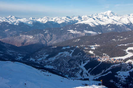Sunset view from the mountain to the valley and city of courchevel with its houses and forest and the ski slopes. Mont Blanc massif in the background. great mood and snowy mountainscape. Stock fotó