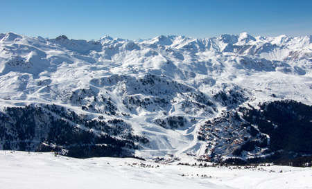 Meribel mottaret skiing area slopes view in the valley and the surrounding mountains of France alps. sun light with a great mood and snowy mountainscape landscape of the French alpes les 3 vallees.