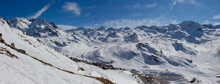 Panoramic View from the mountain over val thorens with aiguille peclet and the glacier of thorens. Beautiful blue sky in perfect sun light with a great mood and snowy mountainscape landscape of the French alpes.