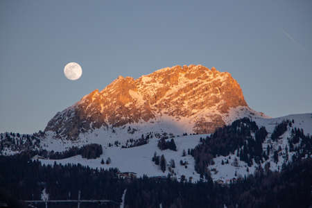 Moon rising and sunset light at the same time in the Italy dolomites val di fassa, sella ronda, sella stock. moon over the mountain and perfect landscape. perfect mood for evening after long skiing day. Standard-Bild