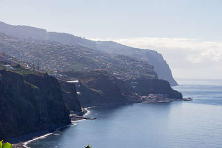 Beautiful madeira coastline with high cliffs, horizon and the sea. Hiking a small trail at the edge of a high cliff at the coastline of madeira, portugal. The waves of the sea crashing at the coastline, the cliff itself very steep and dangerous.