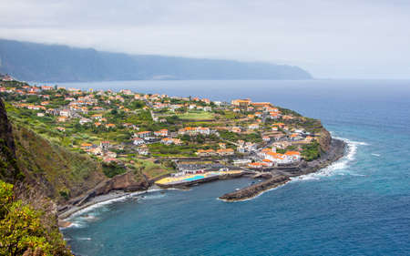 View from the cliffs down to the small city ponta delgada at the north coast of madeira, portugal. Lying on a headland of the island pointing in the sea, high mountains surrounding it, with small typical madeiran villages and houses.