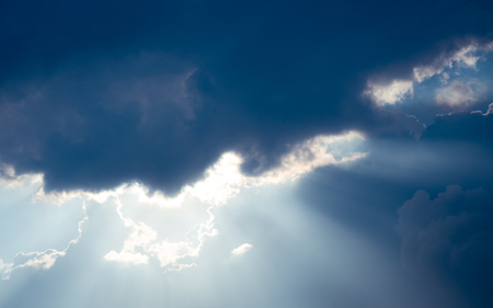 The sun shines through the dark clouds, creating a beautiful beam.
