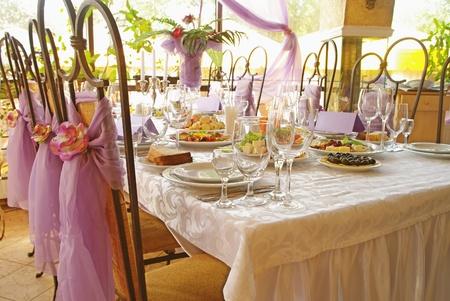 Tabel instellen voor een bruiloft diner versierd met bloemen en een zijde boog