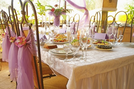 wedding table setting: Table set for a wedding dinner decorated with flowers and a silk bow  Stock Photo